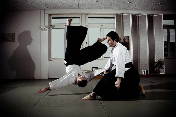 An aikido teacher throwing a student
