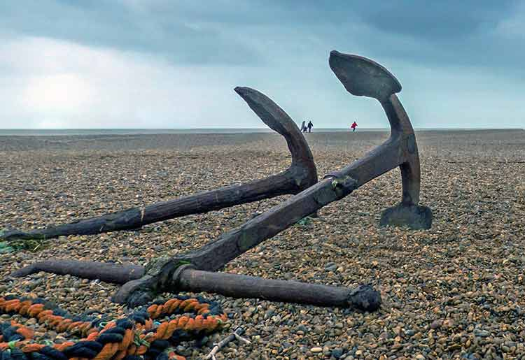 A pair of rusted anchors on a stony beach, with human figures in the far distance