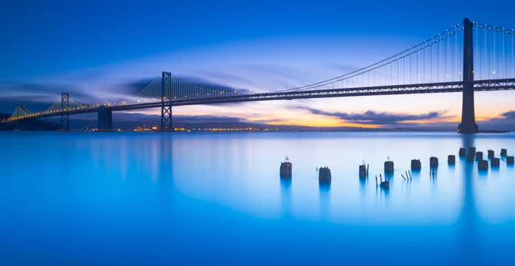 Photograph of San Francisco's Bay Bridge at dawn, with a set of pilings in front