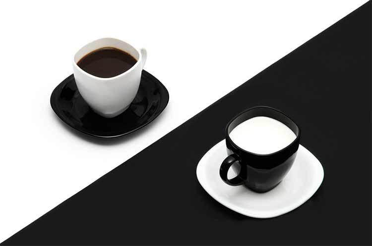 Two coffee cups, one white with dark coffee, one black with milk coffee, set on a black-white diagonal