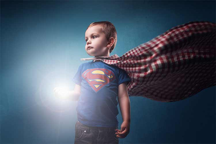Photograph of a young boy in a Superman shirt with a cape made from a tablecloth