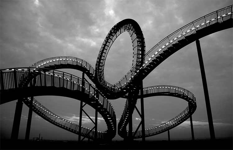 A rollercoaster shot against the sky, photographed in black and white