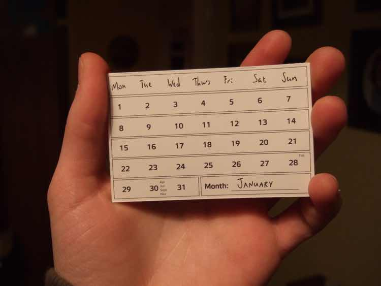 A calendar for the month of January held in a male hand