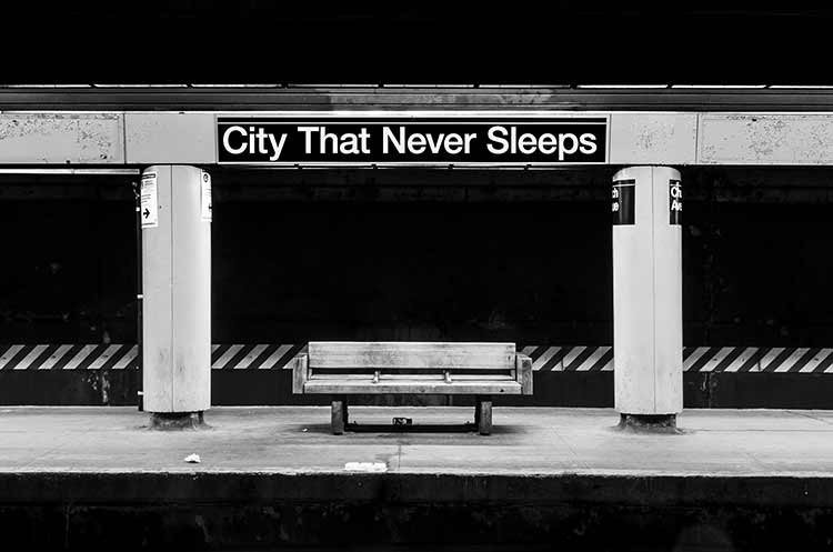 Black and white photograph of a subway seat with 'The City That Never Sleeps' above it