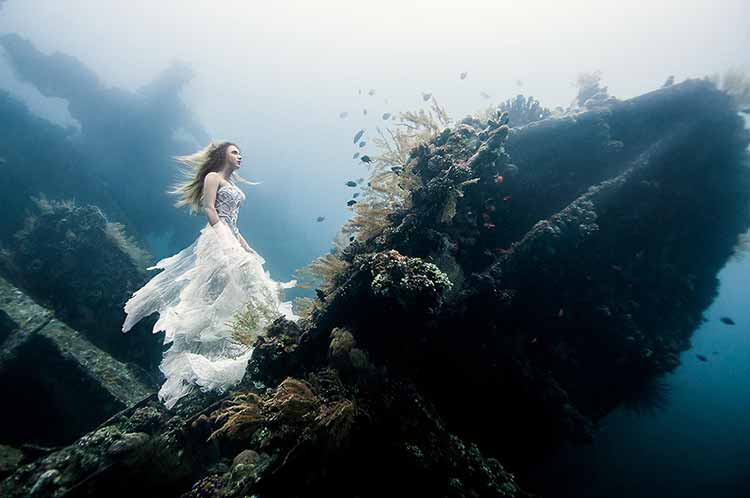 Photograph of a woman in a white dress walking the bow of a sunken ship underwater