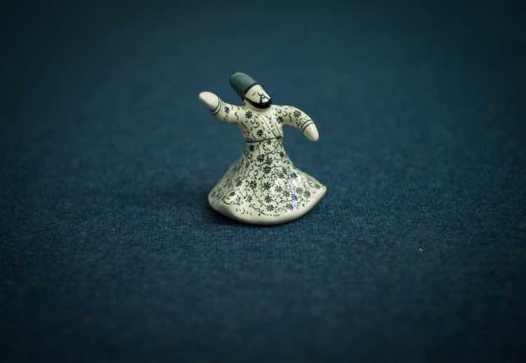 A small ivory statuette of a whirling dervish set on blue cloth