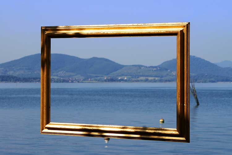 A golden empty picture frame floating in front of a peaceful harbour