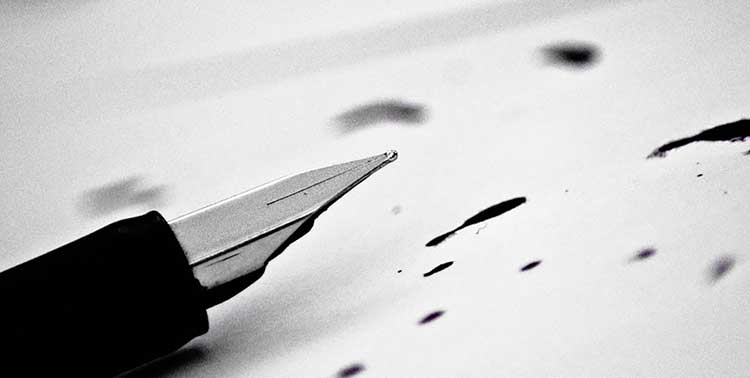 A black-and-white photograph of a fountain pen on a piece of paper with drops of ink on it