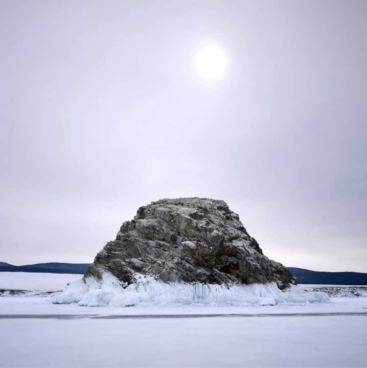 An outcropping of rock surrounded by frozen water, with a pewter sky and sun behind it
