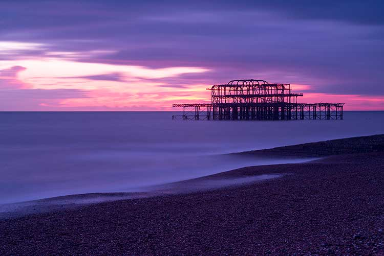 A long-exposure of a metal gantry out at sea under a purple sky and sunset