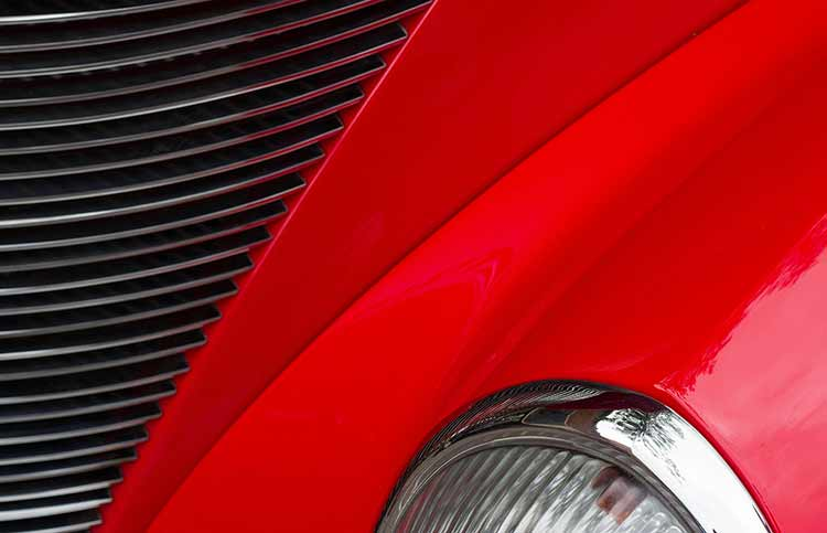 The headlight, grill and red hood of a sports car