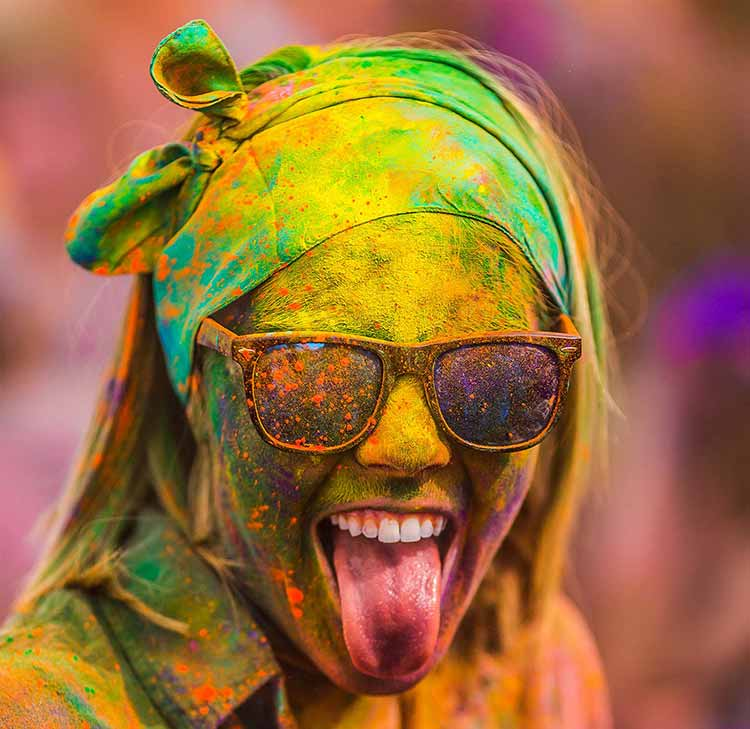 Photograph of a woman's paint-spattered face, wearing sunglasses and smiling with her tongue out during the Indian festival of Holi