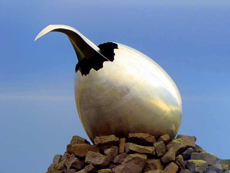 The curved nose of a silver jet emerging from a metallic egg.