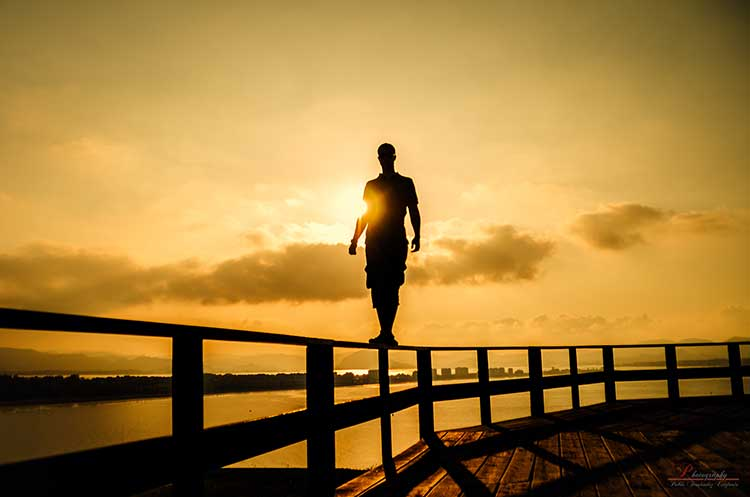 Photograph of a man standing balanced on a railing with a sunset behind him