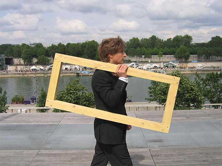 Photograph of a man in a tuxedo carrying an empty wooden frame