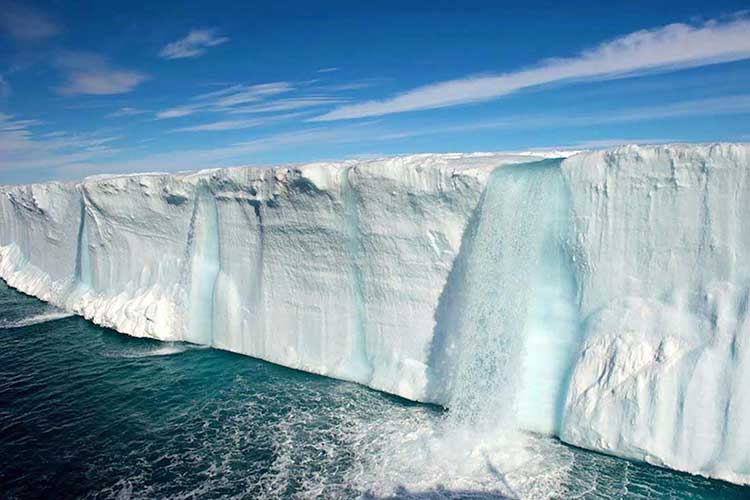 Photograph of an icepack melting into the sea with waterfalls coming off it