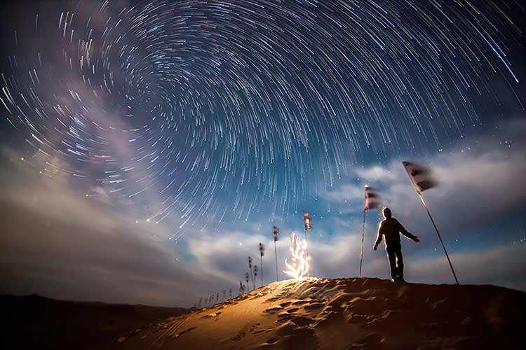 A climber on a snowy mountain under a swirling skyscape of stars
