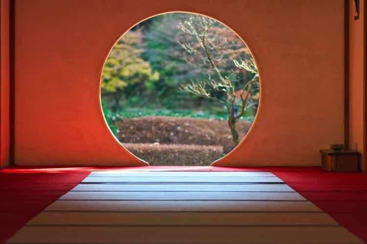 A circular door in a Japanese room looking out onto a garden