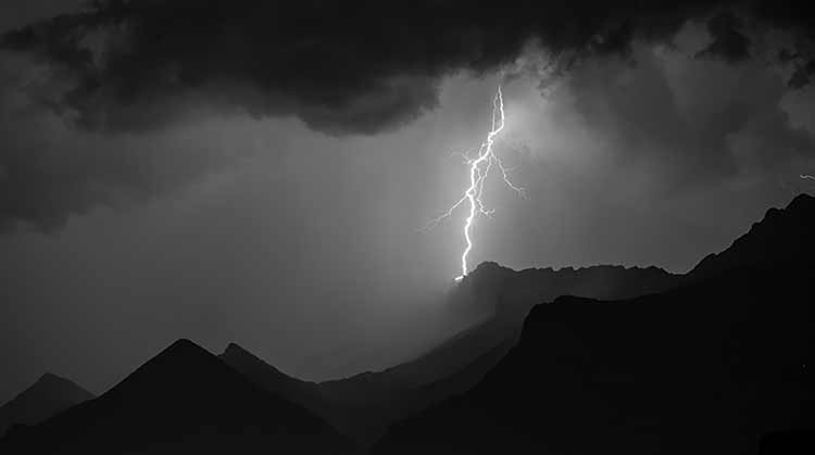 A bolt of lightning against a dark sky and sharp-edged mountains