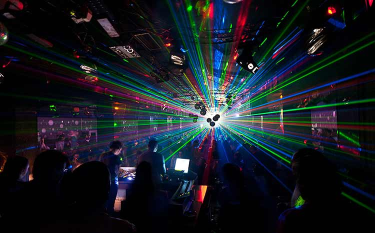 Photograph of DJs framed by lasers inside a Greek nightclub