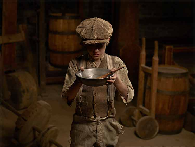 Photograph of a Victorian boy holding out an empty food bowl