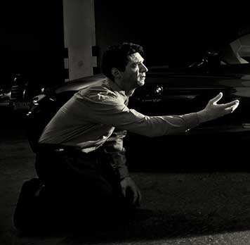 A photograph of a man kneeling in a parking garage, pleading for his life
