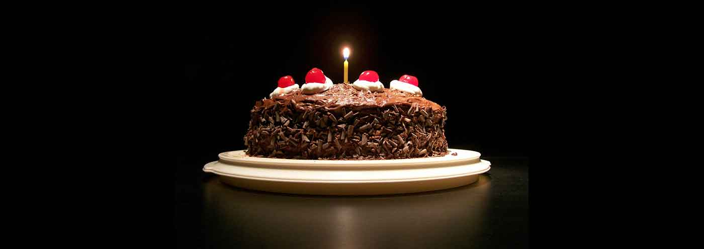 Photograph of a chocolate cake lit by a single candle