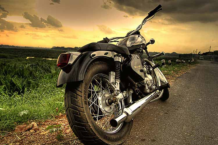 A photograph of a Royal Enfield Motorcycle shot from behind against a rising sun