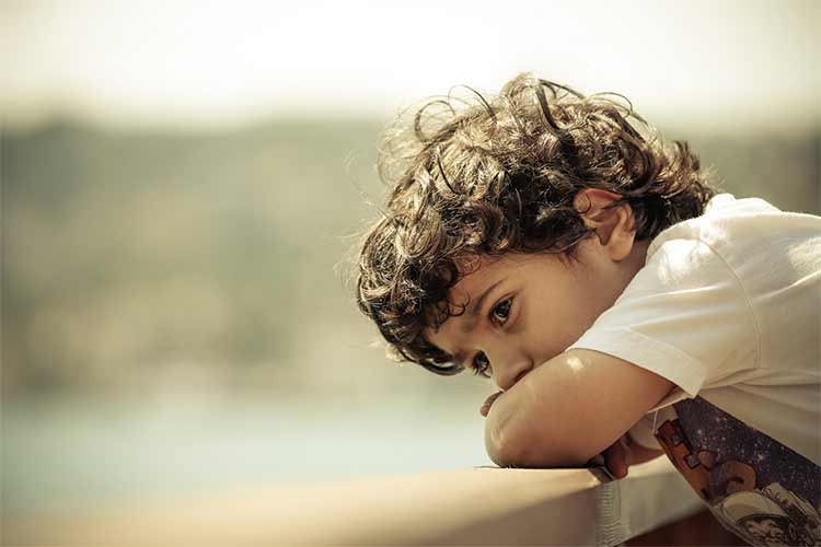 Photograph of a sad young boy leaning on a rail