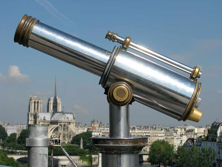 A shiny silver telescope shown over a city