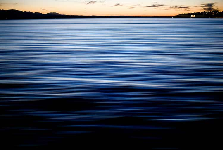 Gentle ripples of blue water in front of a horizon at dawn