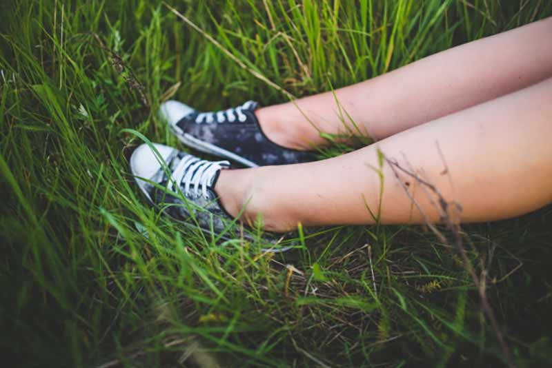 A young woman's legs and sneakers against tall green grass
