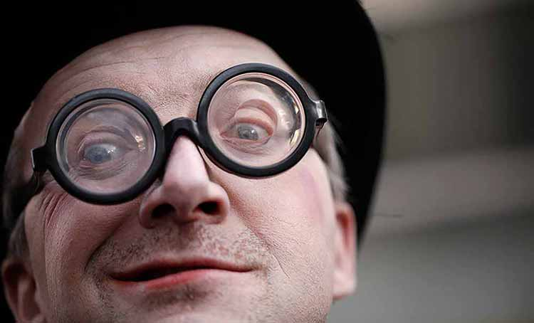 Close-up photograph of a grimacing man with distinctive round thick-framed spectacles