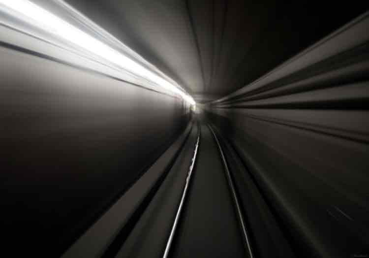 A blurred photograph of train rails in a tunnel
