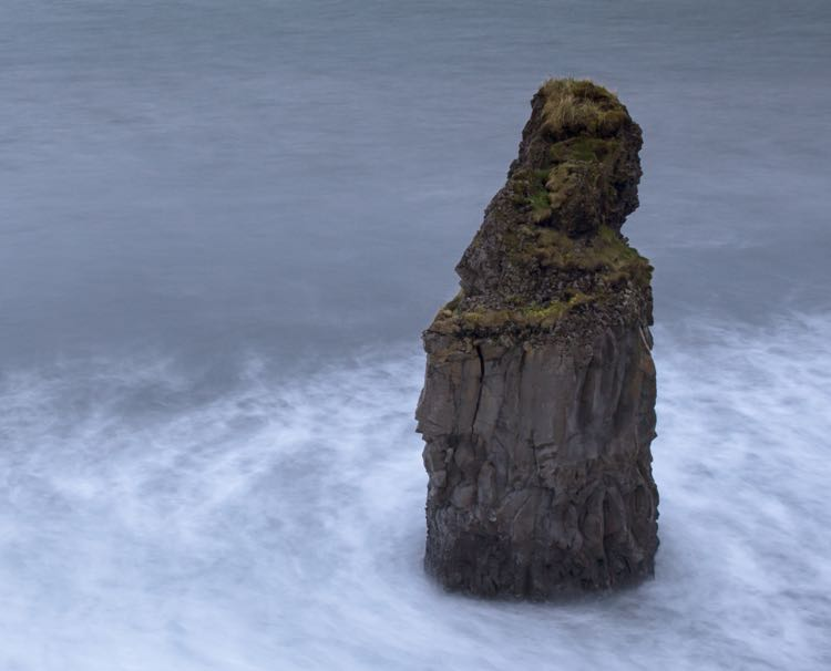 A pillar of rock in a white-blue ocean