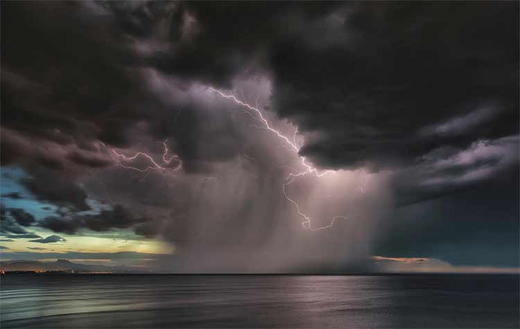 Photograph of lightning from a dark cloud into the sea