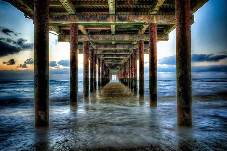 A single-point perspective under a boardwalk, looking out to a blue-green ocean