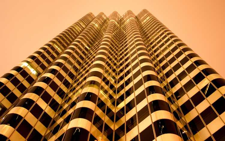 A sepia-toned photograph of a building with a wavy facade, shot from below