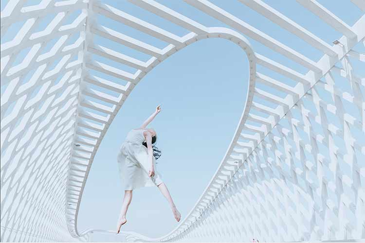 A dancer jumping on a bridge