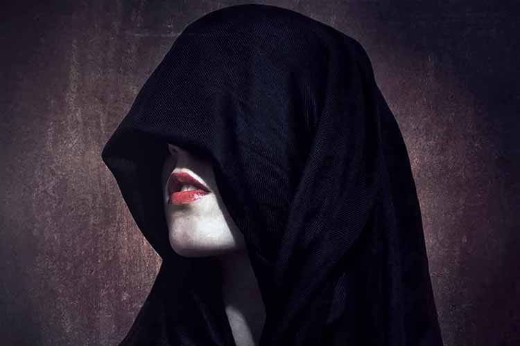 Photograph of a woman's face obscured by a hood