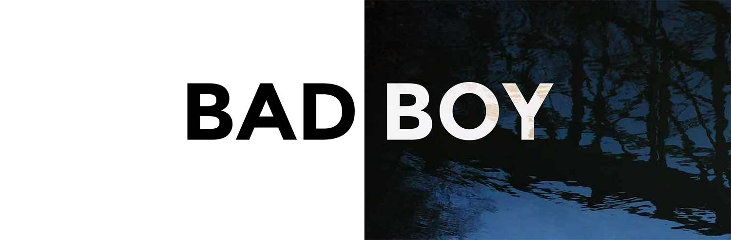 The words BAD BOY, half-black and half-white, set against a photograph of a bridge reflected in a stream