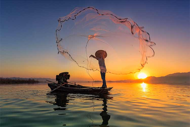 Photograph of a fishing net cast from a sampan on a lake, backlit by the sun, in Guanting, China