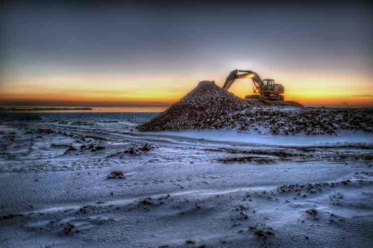 An excavator parked on a mound of snowy earth, with a setting sun behind it