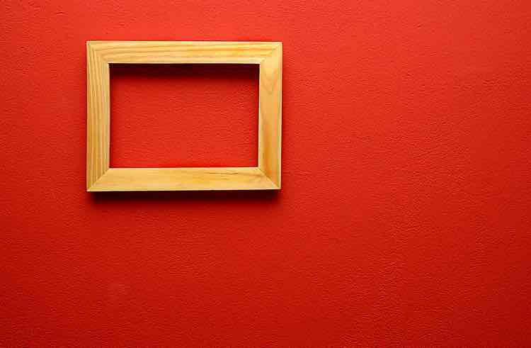 A small emoty wooden frame on a bright red wall