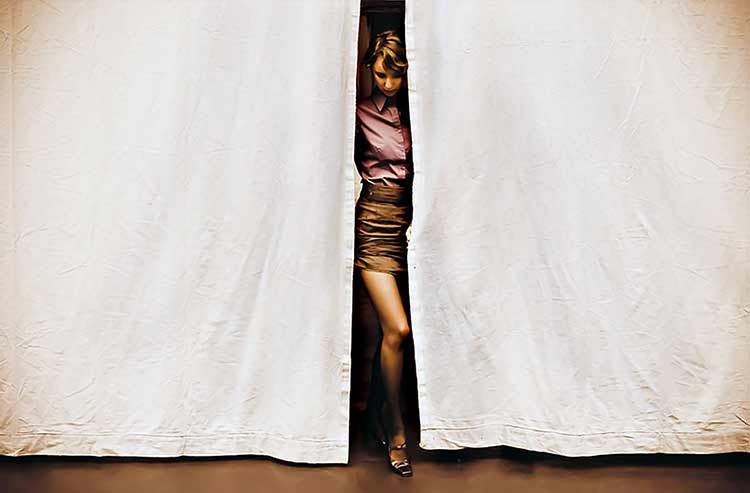 Photograph of woman framed between stage curtains