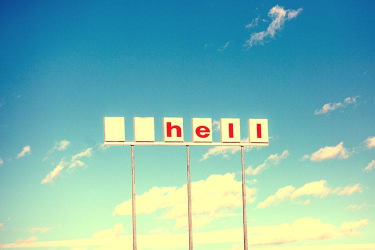 "A sign with missing letters against a bright blue sky. The remaining letters spell out the word ""hell"""
