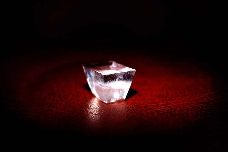 A single icecube spotlight on a red wooden desk
