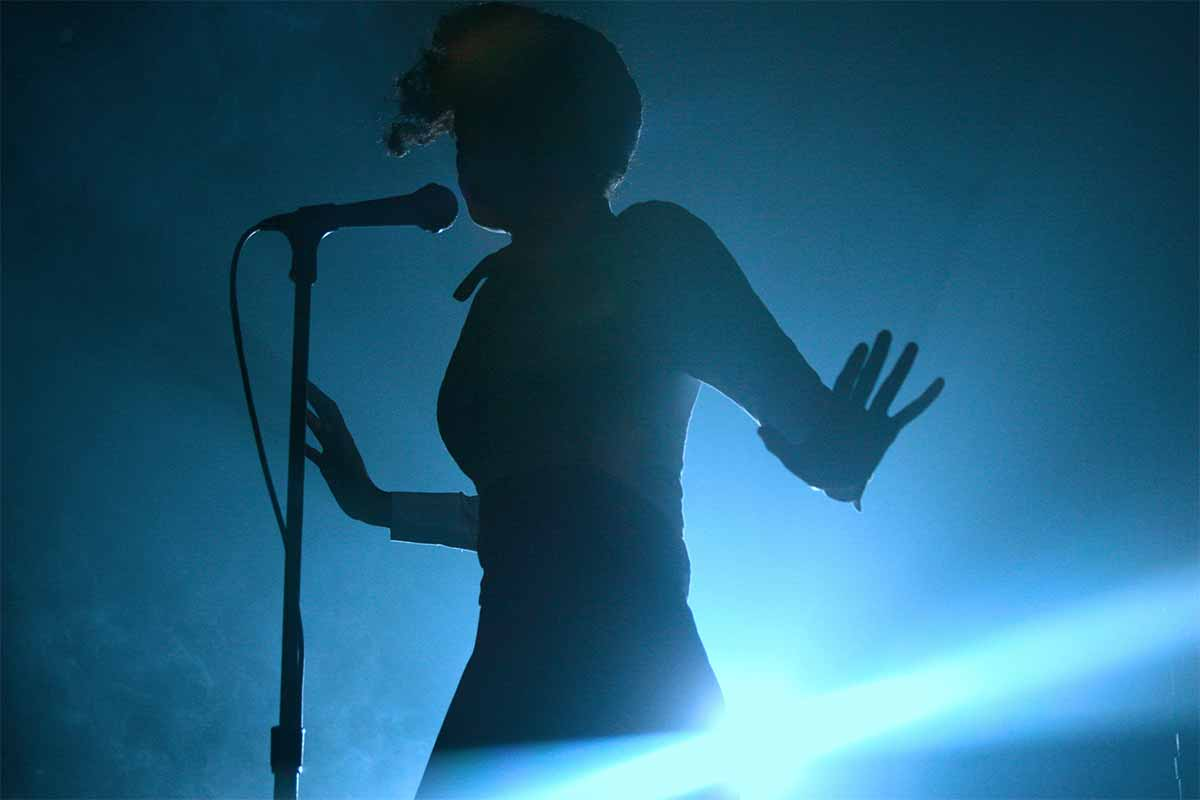 Photograph of Janelle Monáe in concert, shot in silhouette against a blue light