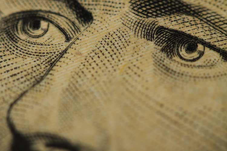 An extremely close up photograph of the face on a US ten dollar bill