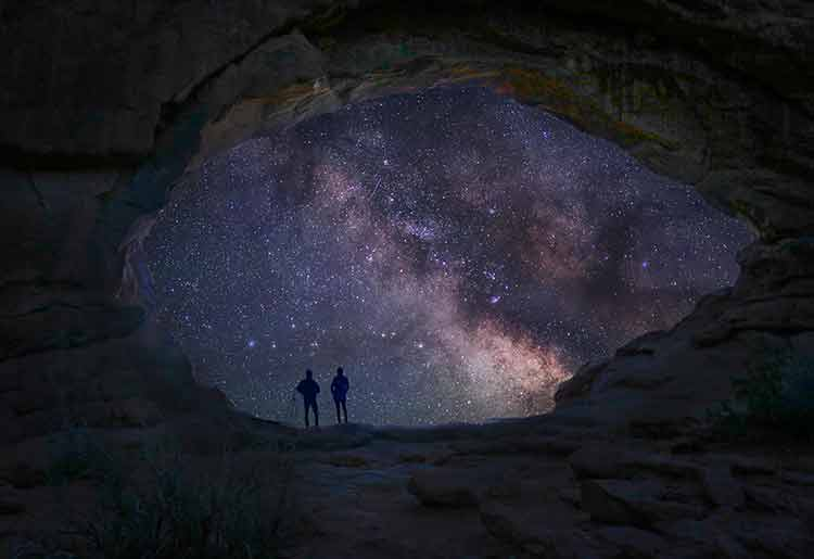 Photograph through the mouth of the North Window cave in Moab, Utah, with two people silhouetted against of the Milky Way
